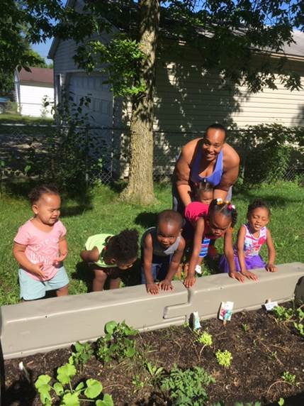 Dayton Ohio's Tumbling Tot's Pre-School Director Kisha Tyree with students at their SNAP Ed Garden.  They started green bean and cucumber seeds, journaled their progress and planted them in the garden along with other seedlings.  All this was part of the SNAP Ed Eat Play Grow program with Katie Schroeder, SNAP Ed Program Assistant in Montgomery County.  You can see by the smiles on their faces that they really enjoyed the project and are looking forward to the harvest!